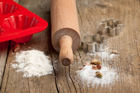 Dough, sugar, wooden rolling-pin and cookie cutters on old wooden table. See series. Stock Photo - 9181242