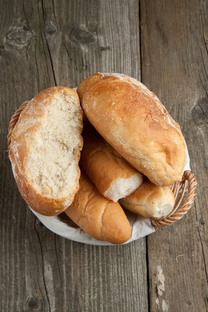 Top view on fresh bread in basket on old wooden table Stock Photo - 9239123
