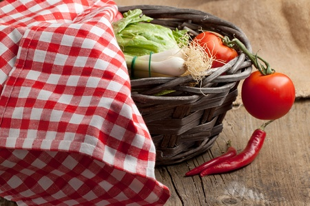 Tomato, green onion, green salad and red hot chili peppers in basket under red and white napkin on old wooden table. See series photo