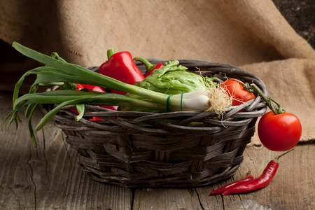 Composition of basket with red paprika, green salad, tomato and red hot chili peppers on old wooden table with sacking as background photo