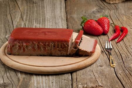 melba: Aperitivo de pat� con fresa jelly, frescas fresas y rojos hot chili peppers en escritorio de madera sobre fondo de madera