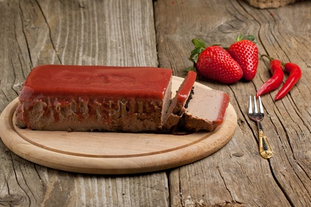 Pate Appetizer with strawberry jelly, fresh strawberry and red hot chili peppers on wooden desk over wooden background photo