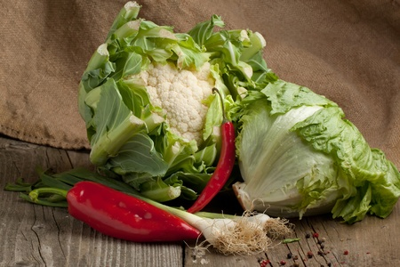 Composition with green salad, paprika, green onion, red hot chili pepper and cauliflower on old wooden table photo