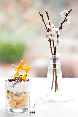 Apple cream dessert in white table with blossom brunch of cherry photo