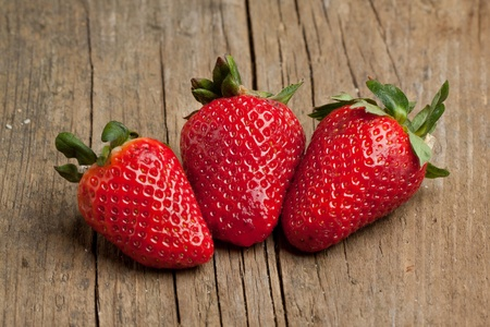 Three fresh strawberries on old wooden background Stockfoto