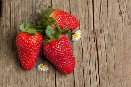 frutillas: Tres fresas frescas con remolcar poco flores blancas sobre fondo de madera vieja