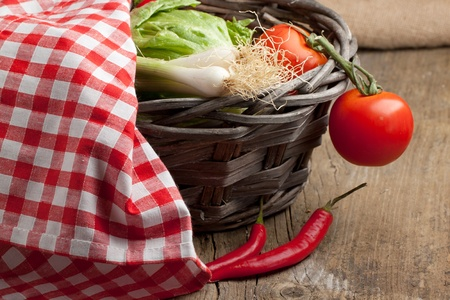 Basket with tomato, green onion and red hot chili peppers under red and white napkin. See series photo