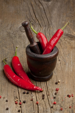 Red hot chili peppers in old wooden mortar and mix of dry pepper on old wooden table