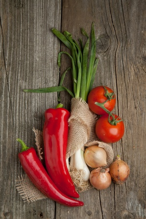Bovenaanzicht op tomaten, uien en paprika op oude houten tafel Stockfoto