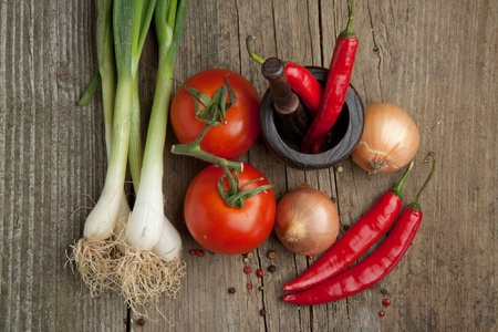 Top view on tomato, onions and red hot chili peppers in old mortar on old wooden table photo