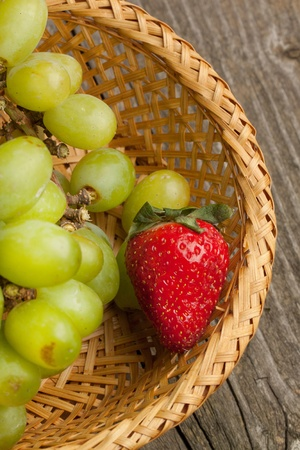 Green grapes and strawberry in basket on wooden table photo