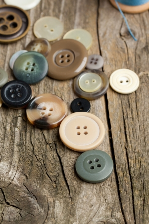 Collection of various buttons on old wooden table photo
