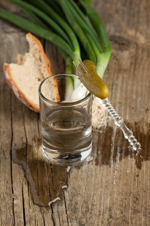 distilled alcohol: Glass of vodka with cucumber, onion and bread on old wooden table Stock Photo
