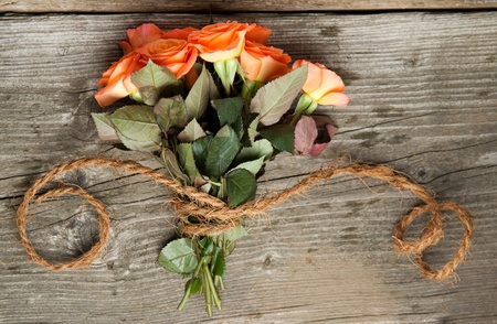 Top view on bunch of orange roses with cord on old wooden table photo