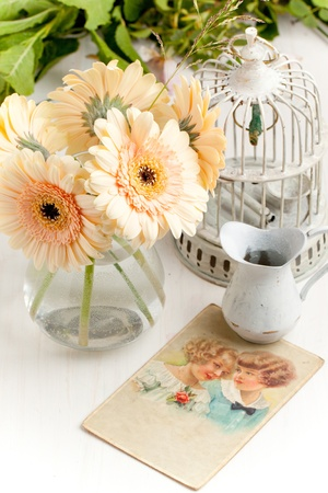 Bunch of gerbera flower with old vintage cage, gift card and little jug on white table photo