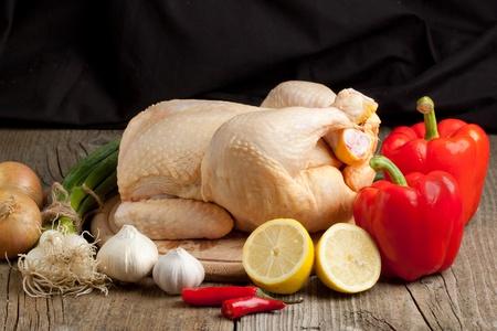 pollo rostizado: Composición con pollo crudo, cebolla, ajo, pimentón rojo y limón en la tabla de madera Foto de archivo