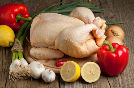 Zusammensetzung mit rohem Huhn, Zwiebel, Knoblauch, roter Paprika und Zitrone auf alten Holztisch