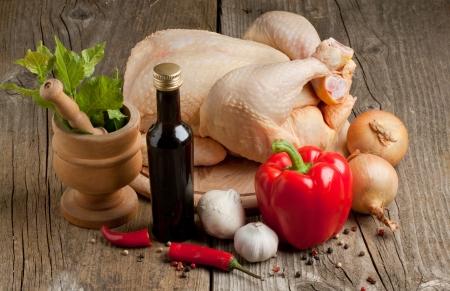 Composizione con pollo crudo, cipolla, aglio, peperoni rossi e malta d'epoca sulla vecchia tavola di legno