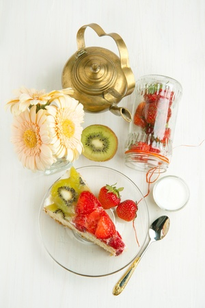 Top view on piece of homemade fruit cake with strawberries and kiwi, glass jar of strawberries and old vintage teapot on white wooden table photo