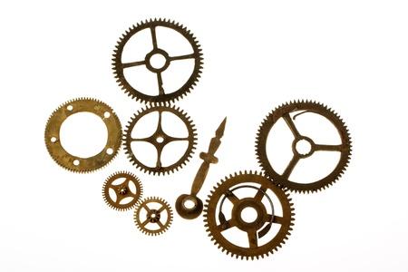 Antiguo mecanismo de relojería con dientes de metal de latón sobre fondo blanco Foto de archivo
