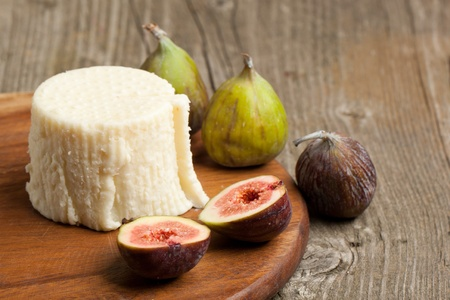 ripened: Wooden plate with white cheese and fresh figs on old wooden table