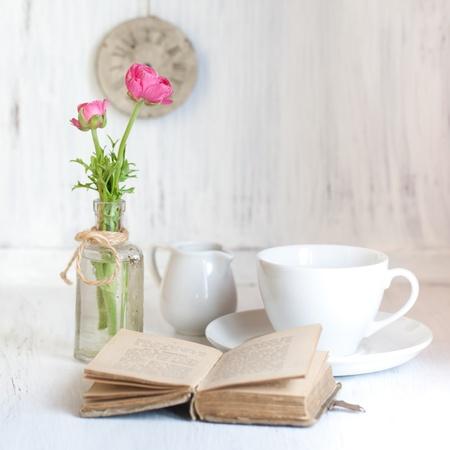 Tow fleurs roses Renoncules dans un vieux flacon, livre de cru ouverture vieux et tasse de thé sur la table en bois blanc