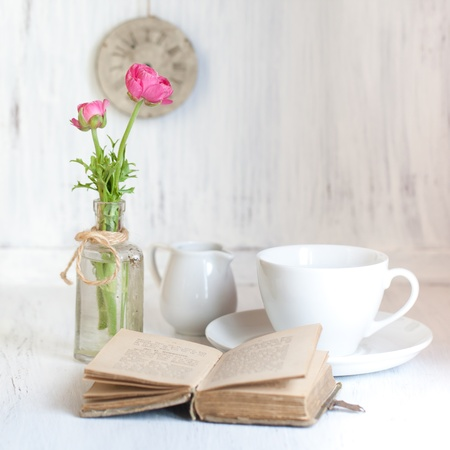 vintage bottle: Tow pink flowers ranunculus in old vintage bottle, old opening book and cup of tea on white wooden table