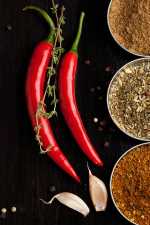 pepper grinder: Red chili peppers, garlic and mix of spices on black table Stock Photo