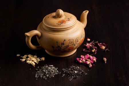 sencha: Ceramic teapot with dry tea variation on black table