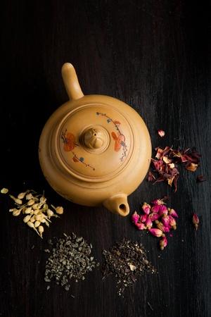 Bovenaanzicht op keramische theepot met droge thee variatie op zwart