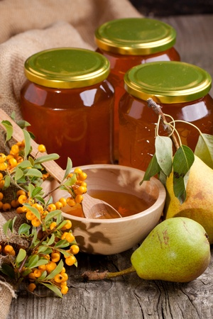 Pots and bowl with fresh honey, pears and orange berries on old wooden table