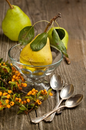 Composition with fresh pears, orange berries and silver teaspoons on old wooden table Stock Photo - 10286165