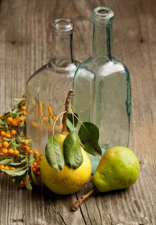 pera: Composici�n con peras frescas, bayas naranjas y botella de vidrio vintage de remolque en mesa de madera vieja