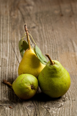 Three fresh pears on old wooden table photo