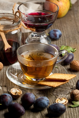 Cup of tea with berry jam and fresh fruits on old wooden table  photo