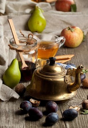 Чаепитие со свежим различных фруктов, старой золотой чайник и стеклянную банку с вареньем в старом деревянном столе