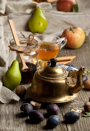 Tea drinking with fresh various fruits, old golden teapot and glass jar of jam in old wooden table photo