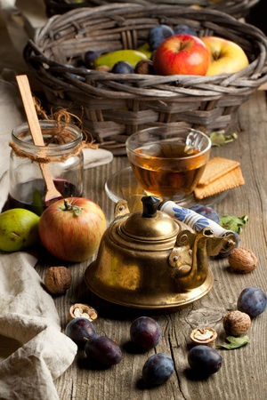 Tea drinking with fresh various fruits, old golden teapot and glass jar of jam on old wooden table