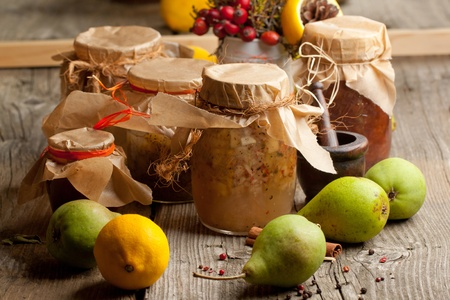 Jam in jars and fresh pears and lemon on old wooden table photo