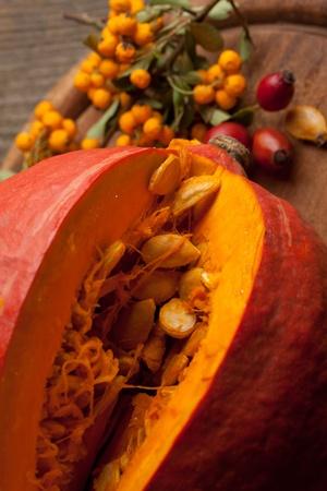 Slised orange pumpkin with seeds on old wooden table photo
