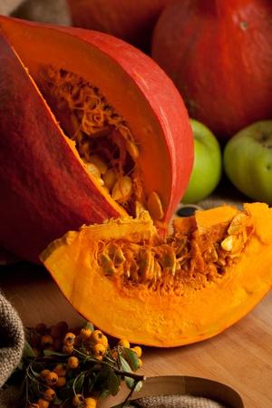Piece of orange pumpkin on wooden desk photo