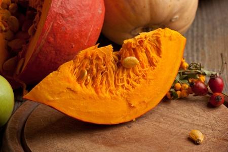 Piece of orange pumpkin on old wooden desk photo