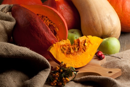 Piece of orange pumpkin with other pumpkins, apples and berries on sacking photo
