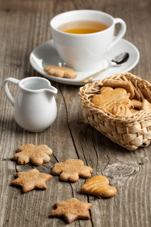 Galletas caseras de azúcar con jarra de leche y una taza de té en la mesa de madera vieja
