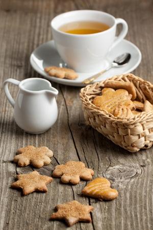 Huisgemaakte suiker koekjes met melk kan en kopje thee op oude houten tafel