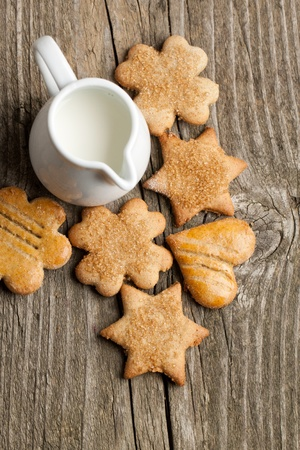 Top view on homemade sugar cookies and jug of milk on old wooden table Stock Photo - 10849187