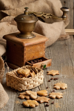 Homemade sugar cookies with vintage grinder and coffee beans on old wooden table photo