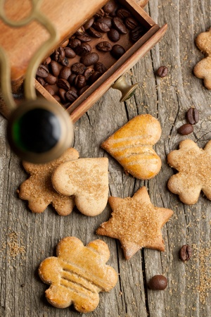 Top view on homemade sugar cookies and grinder with coffee beans on old wooden table photo