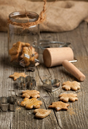rollingpin: Homemade sugar cookies with metal cookie cutters and rolling-pin on old wooden table Stock Photo