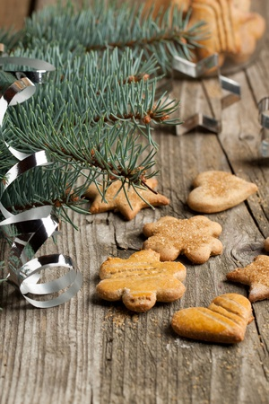 Homemade sugar cookies near christmas tree on old wooden table photo